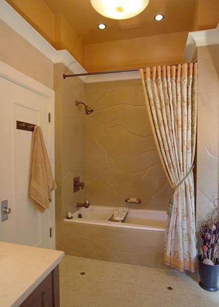 This tub has a limestone slab surround with custom curtain.