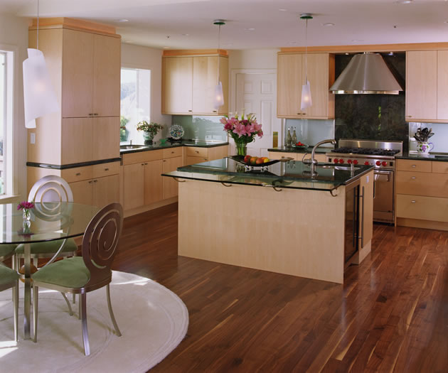 The simple maple cabinetry is contrasted by the dark granite counters and walnut floors.