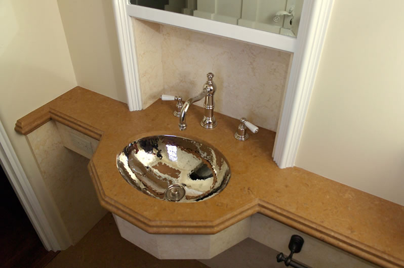 The hammered nickel sink area is recessed into the wall to save space.