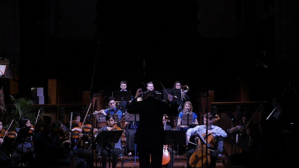 Music Director Jordan Randall Smith leads the orchestra in Bentz's  Approaching Eternity.