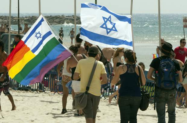 Israelis wave their national flag along with a rainbow flag during the annual Gay Pride parade in Tel Aviv on June 11, 2010, as thousands turned out for the city's gay festival. JACK GUEZ/AFP/Getty Images
