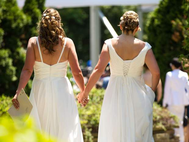 Cheryl Taylor and Jennifer Smith hold hands as they arrive for the Grand Pride Wedding, a mass gay wedding at Casa Loma in Toronto, Canada, on June 26, 2014. GEOFF ROBINS/AFP/Getty Images