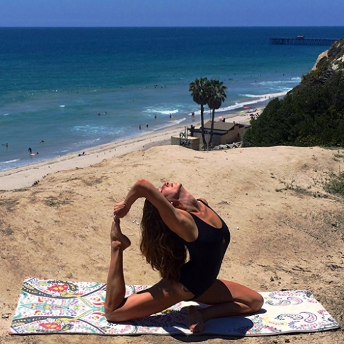 A bright, festive Vagabond Goods mat is the perfect beach-side yoga accessory. Bodysuit by Shakti Wear.