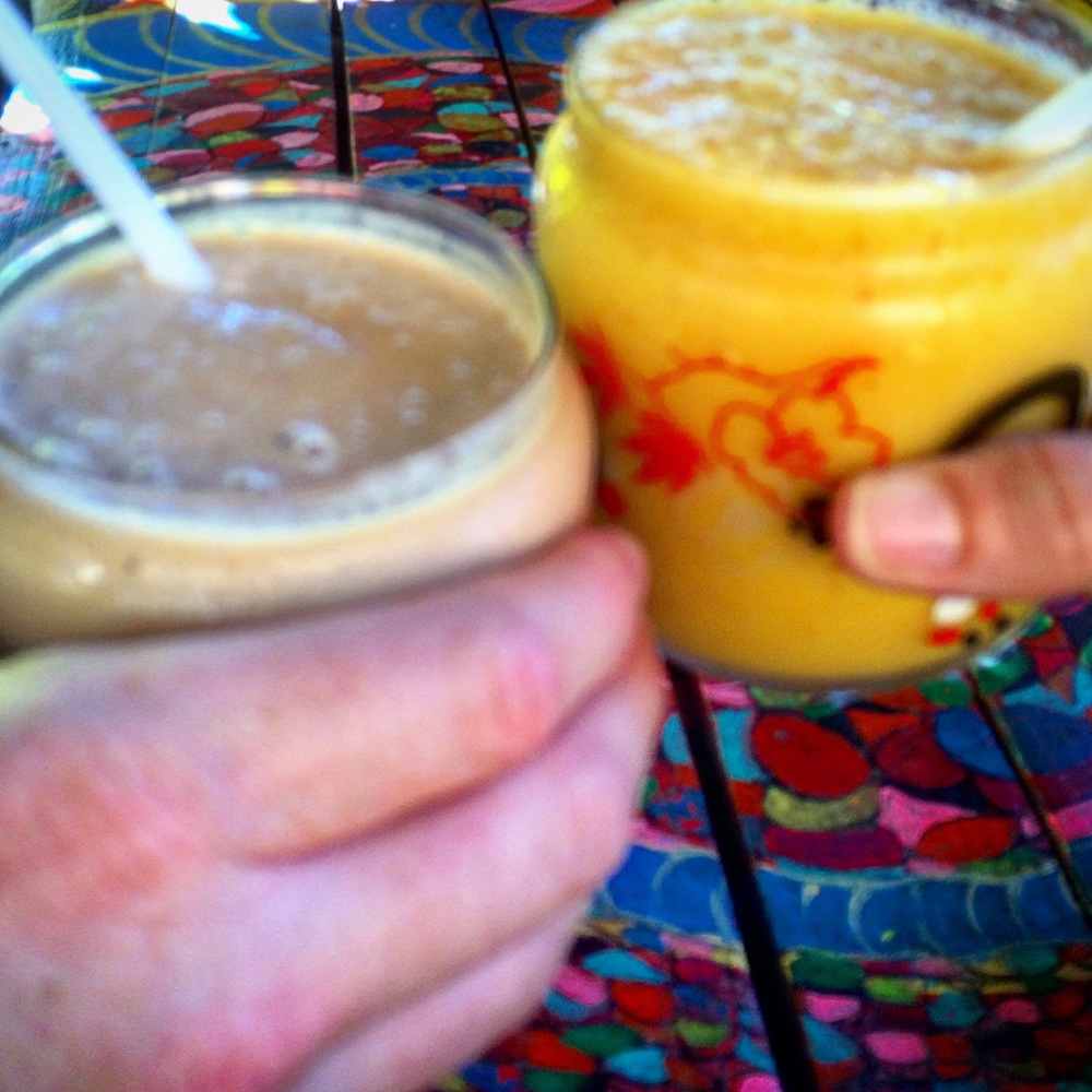 Cheers to your health! Left: Power protein smoothie with veg protein, banana, coconut milk, cinnamon, & cashew nuts. Right: Spicy Share: Pineapple, chili, lime juice, and mango.