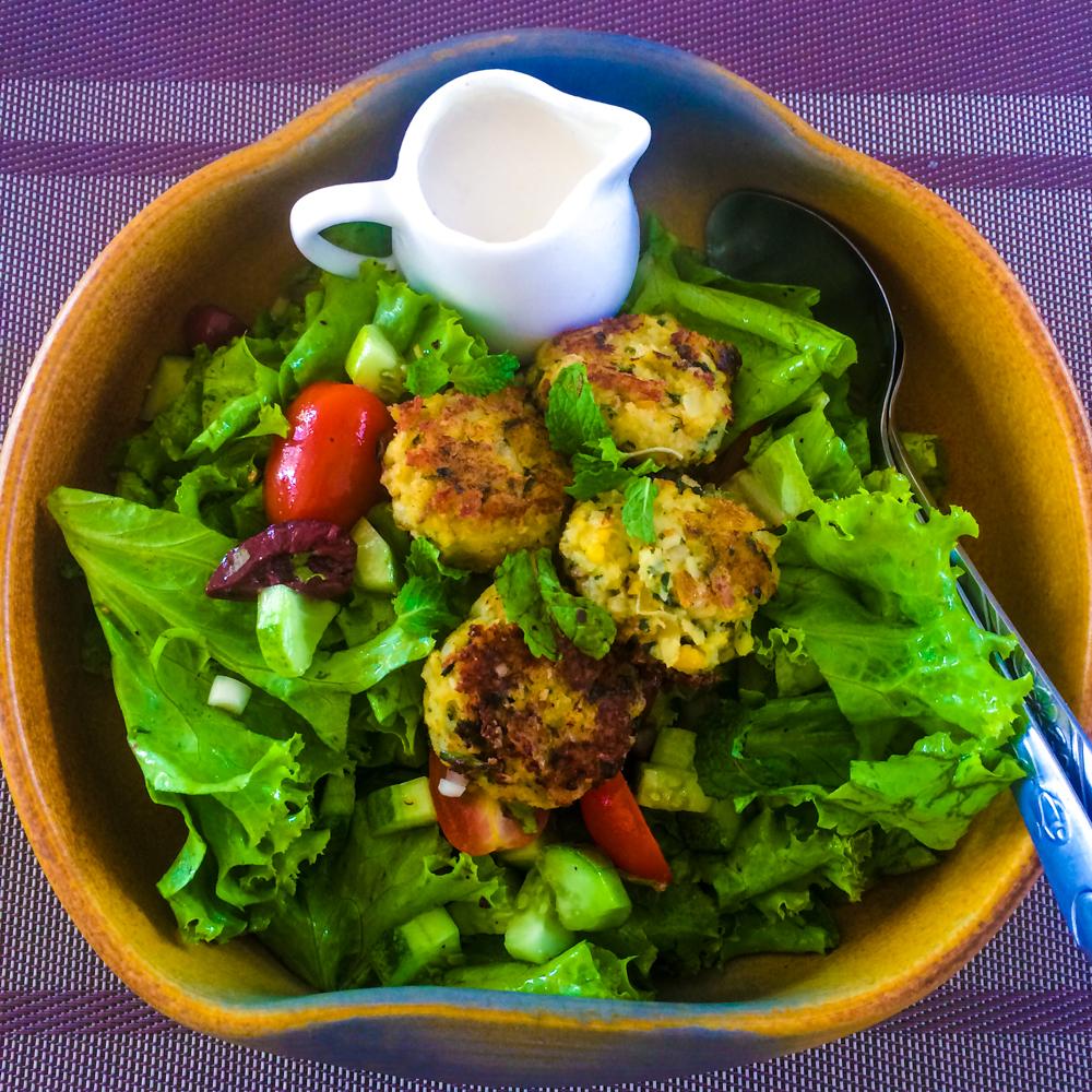 Make Falafel Not War Salad - Crispy cumin & coriander falafel with lettuce, tomato, red onion, cucumber, black olives & tahini garlic dressing.