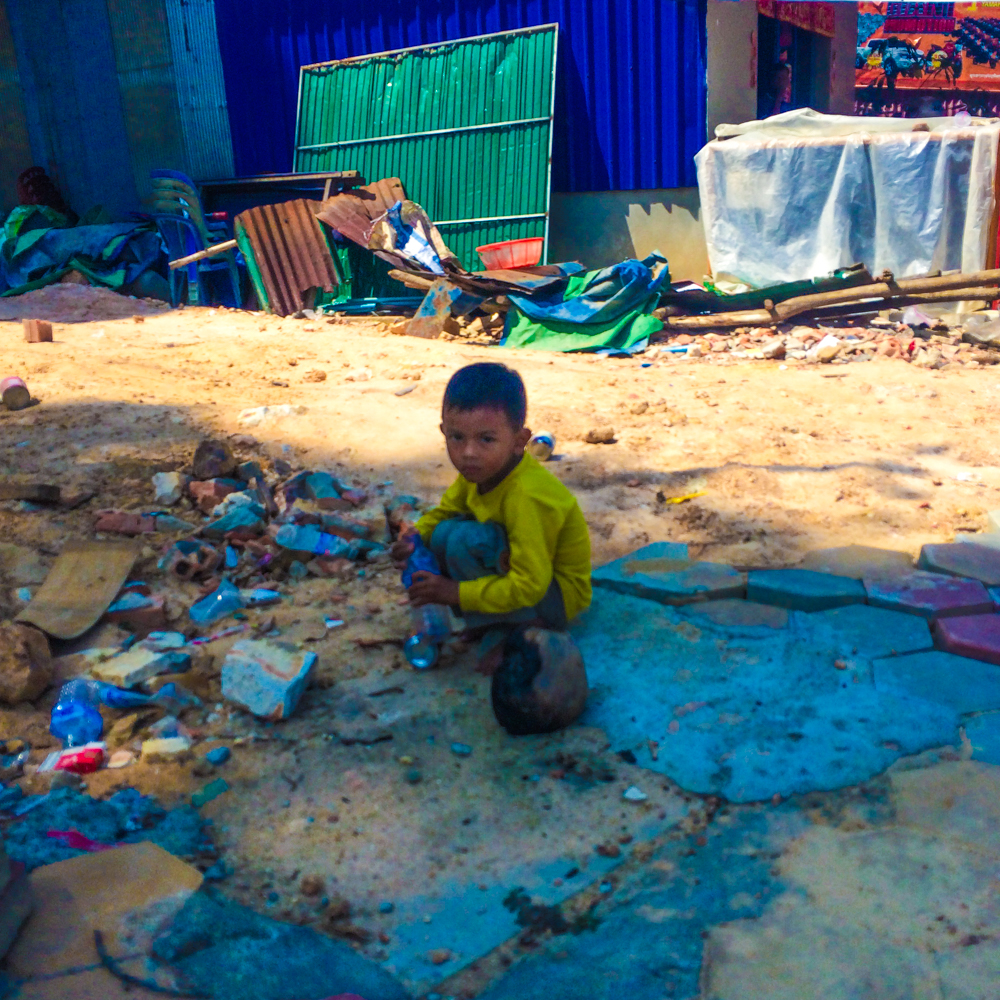 A child plays with trash on the side of the road in Sihanoukville, Cambodia.