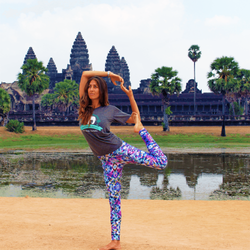 Standing Mermaid Pose (a variation of Dancer's Pose) on the field in front of the temples.