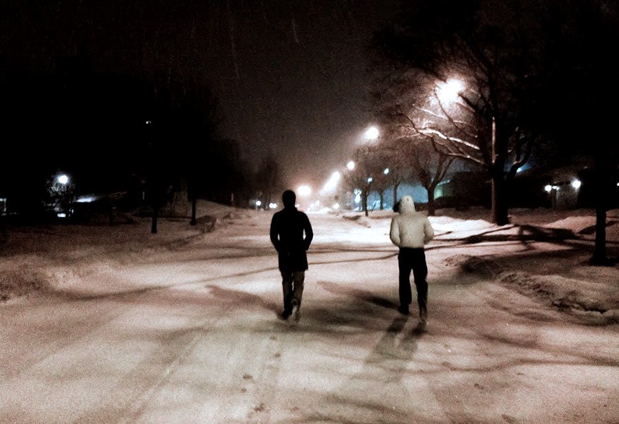 Two guys walking in the snow at night towards the store