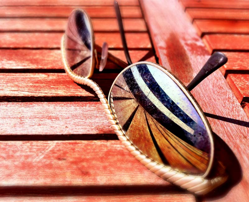 Sunglasses on a table with a reflection shot by Dennis Marciniak of denMAR Photography