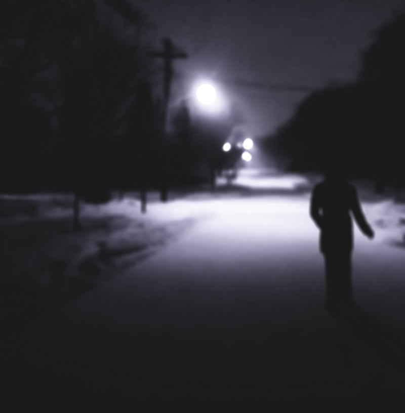 A man walking at night shot out of focus during the Winter in Canada