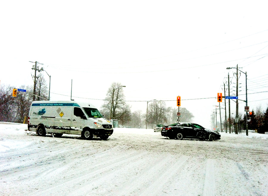 Driving in the snow during a blizzard at a major intersection in Toronto Canada in 2013
