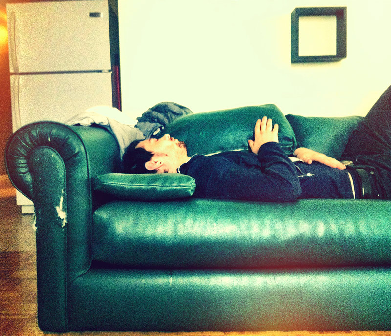 A guy sleeping on the couch after a long night of partying.