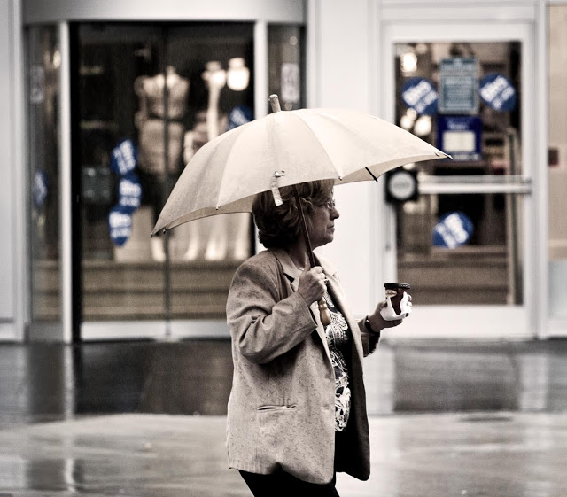 A woman with an umbrella walks through the streets of downtown Toronto enjoying her Tim Hortins coffee