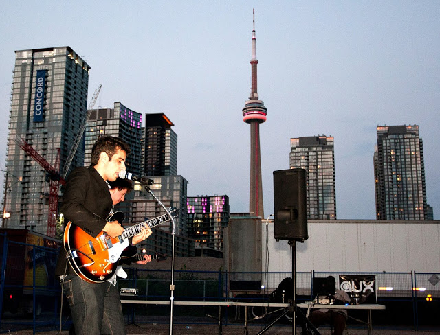 CN Tower in the background of an Indie band playing