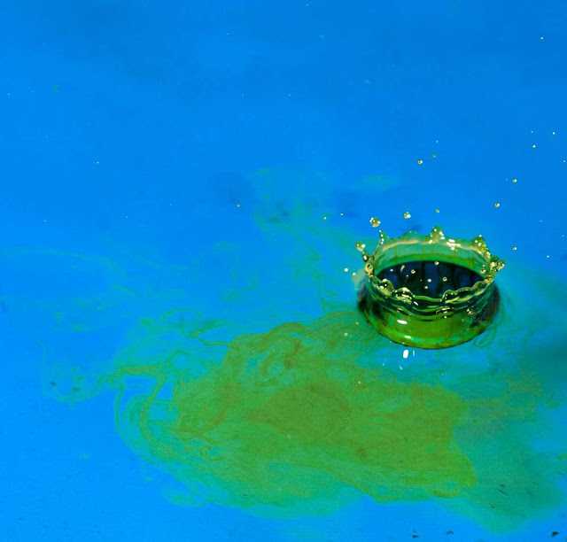 A green waterdrop hitting the surface of some blue water as seen by Dennis Marciniak