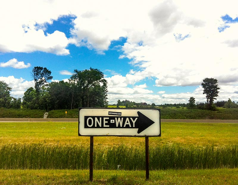A inverted coloured one way sign at a rest stop in Ontario Canada on highway 400