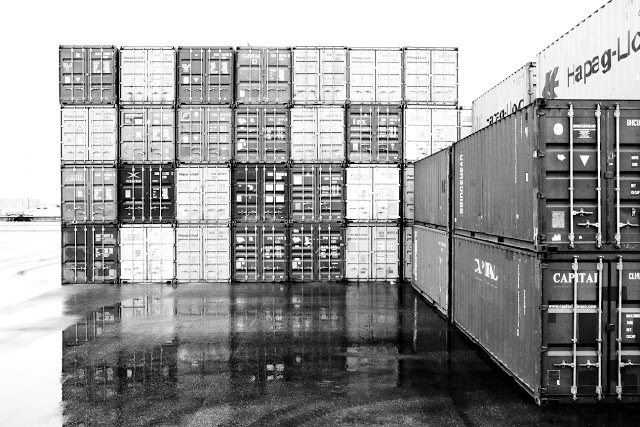 A shipping container stack in a yard in Toronto Ontario Canada shot on a rainy day in black and white.