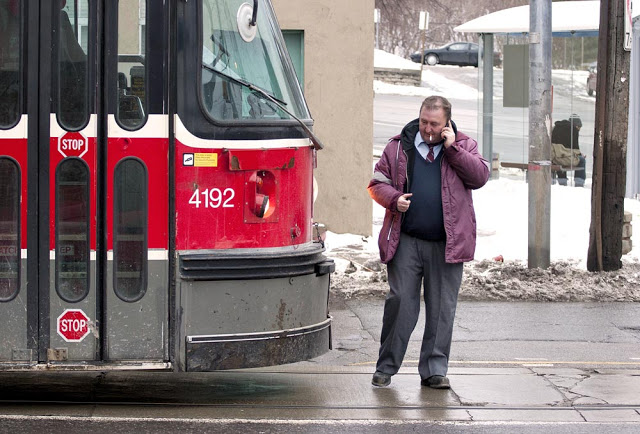 A Toronto streetcar driver stops for a smoke break in front of his streetcar