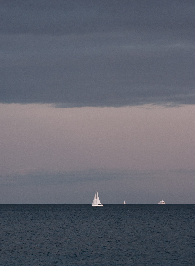 A boat sailing away on Lake Ontario near a harbour in Toronto