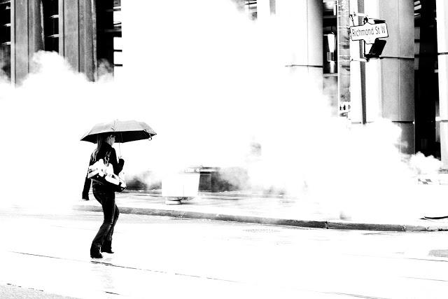 A girl with an umbrella crossing on a rainy day in Toronto at Richmond St. while smoke emits from the ground