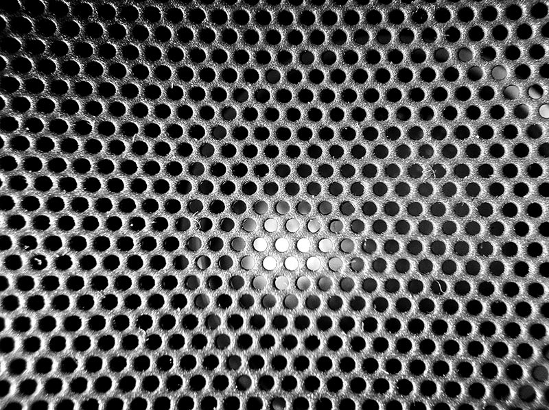 A black and white macro of a speaker grate or cover texture