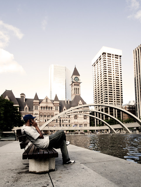 A gentleman sits and makes a phonecall at Nathan Philips Square in Toronto