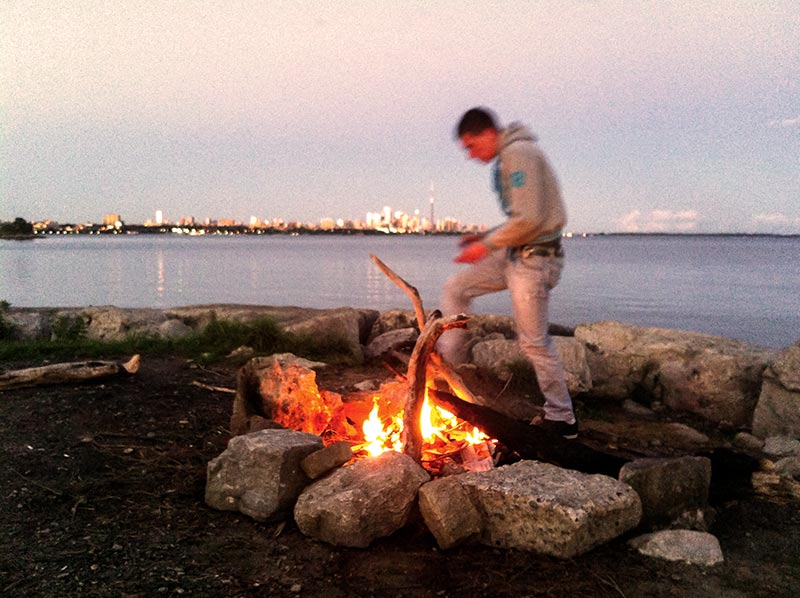 Burning firewood at sunset with the Toronto city skyline behind it