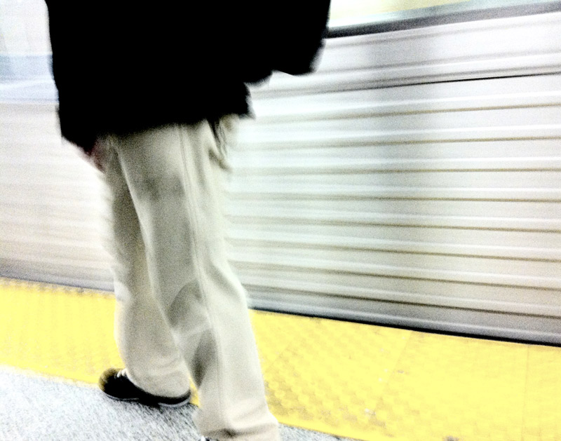 A man on the TTC yellow line on the subway platform in Toronto