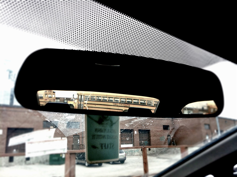 Schoolbus in Rearview while waiting in a parking lot