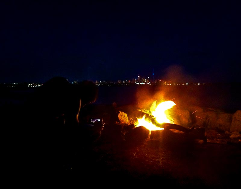 A couple of friends burning some fire infront of the Toronto cityscape