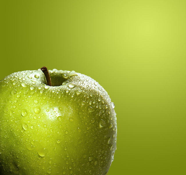 A green apple on a green background misted with water