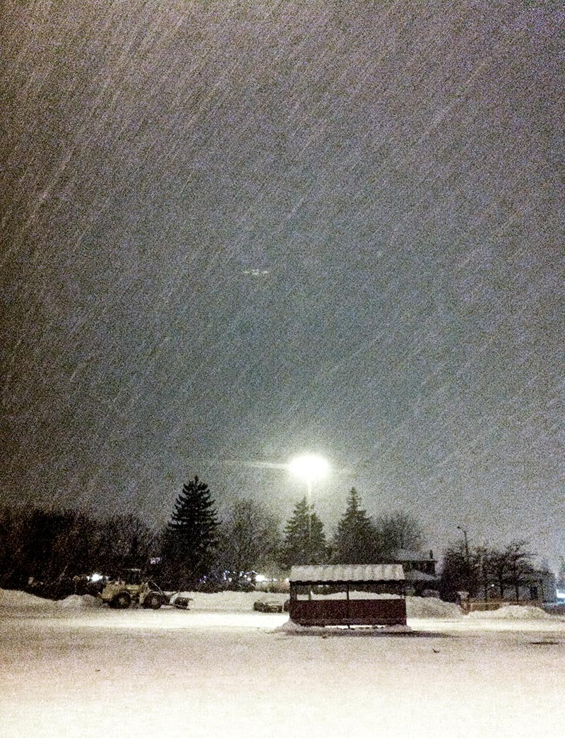Snow falling in Canada overnight in a parking lot of a grocery store