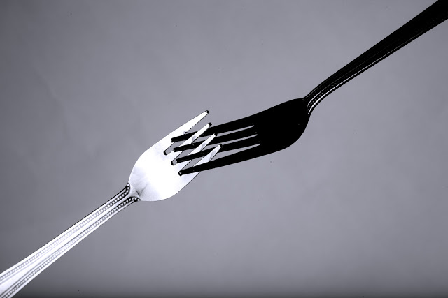 Two forks shot in a studio, one is black and one is white.