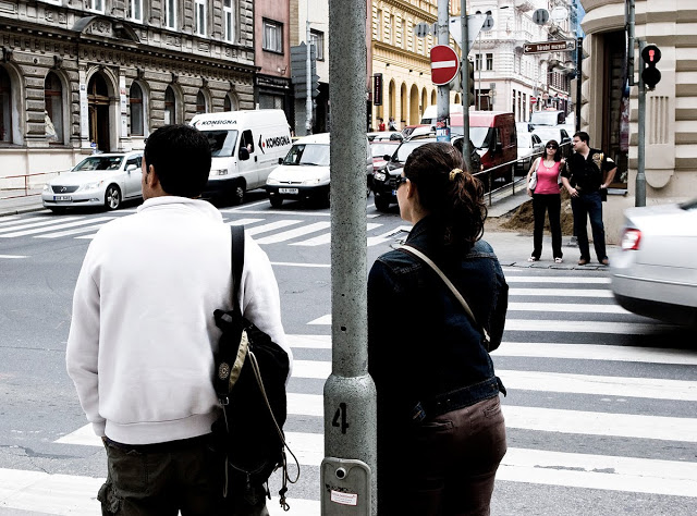 Two couples crossing at an intersection in Prague