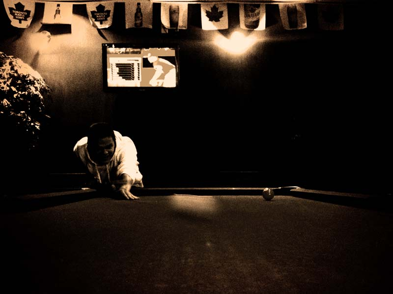 A man hits a cue ball across the table at a bar