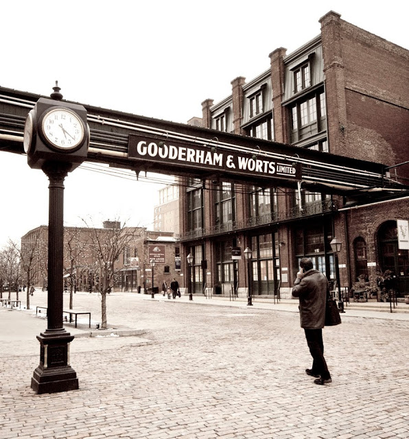 A man walking through the distillery district in Toronto.