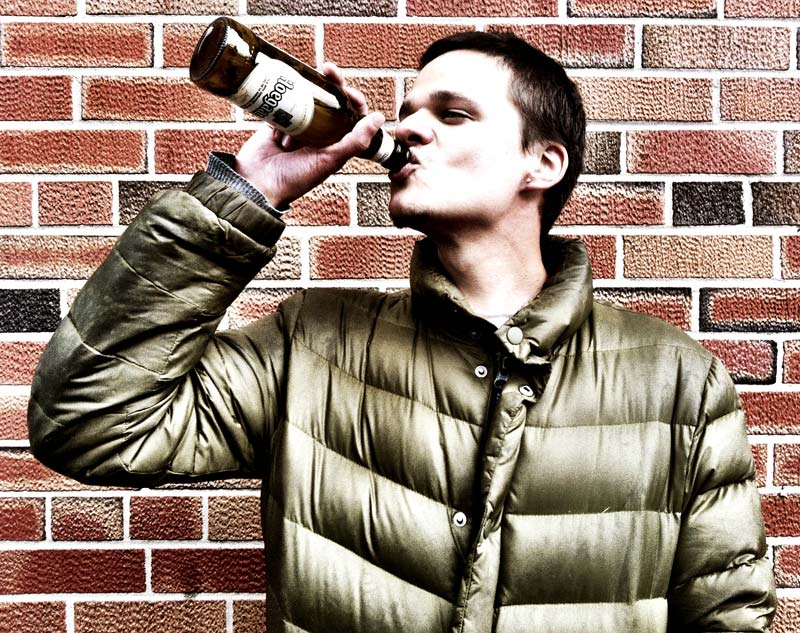 A portrait of a person drinking at a brick wall shot on the iPhone by Dennis Marciniak of denMAR Photography