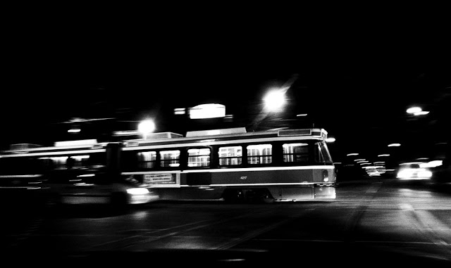 A Toronto Transit Commision TTC street car moving across an intersection at night.