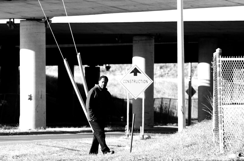 A man waiting for the bus under highway 427 in Toronto