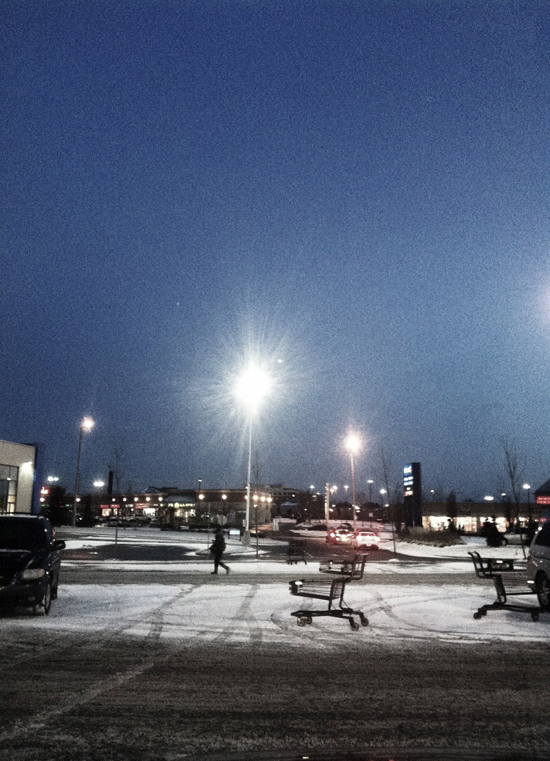 A shopping cart in a parking lot of a snowy plaza