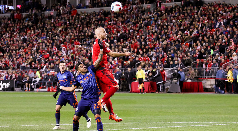 Michael Bradley goes for the header despite an New York City FC attempt to play the space inside the 18 yard box during the Eastern Conference MLS Cup Semifinal. Photo by Dennis Marciniak of denMAR Media.