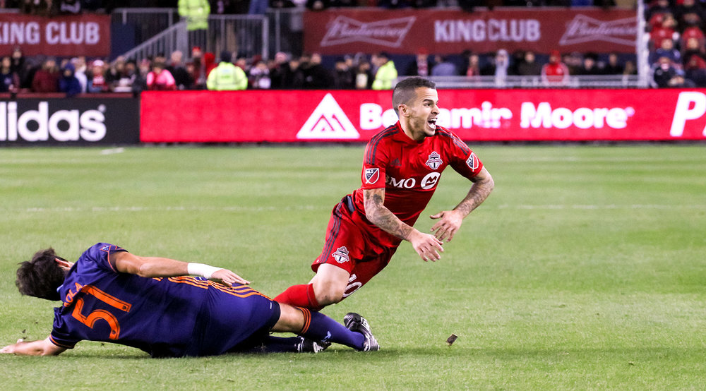 Sebastian Giovinco is taken to the ground by a NYCFC player during a 2016 playoff game. Photo by Dennis Marciniak of denMAR Media.