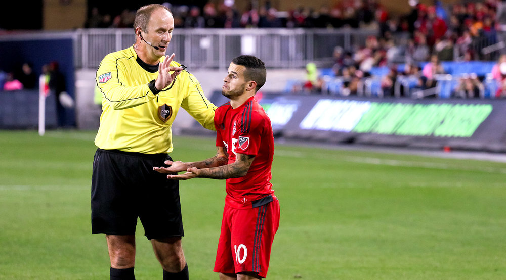 Sebastian Giovinco sticks his arms out in frustration over first official Silviu Petrescu calls over the night during a 2016 MLS playoff game. Photo by Dennis Marciniak of denMAR Media.