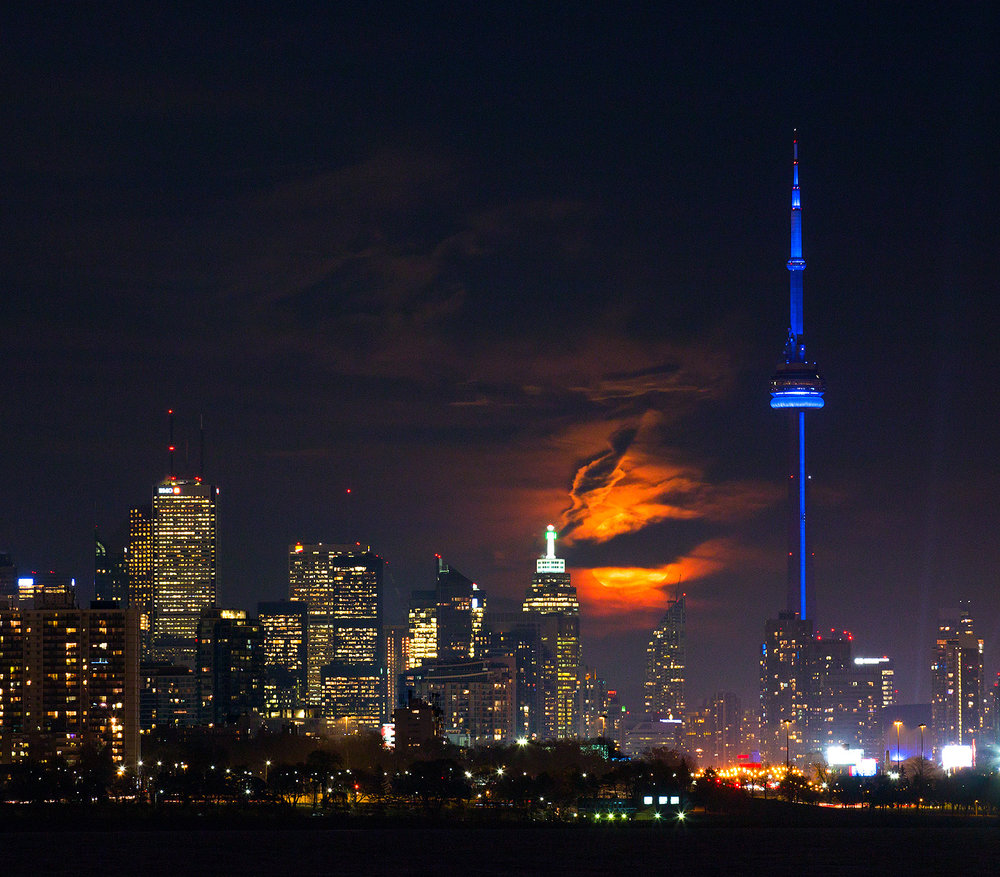 The 2016 Toronto Supermoon taken on November 2016. The moon behind clouds overlooks the CN tower which is lit in blue.
