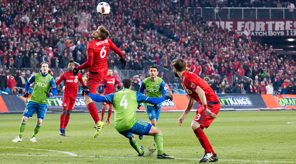 Nick Hagglund leaps over Tyrone Mears to try to get a header on the ball in the first half of the 2016 MLS Cup Final. Image by Dennis Marciniak.
