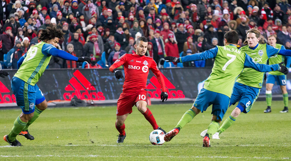 Toronto FC's Sebastian Giovinco tries to play the ball around two Seattle Sounders defenders at the MLS Cup at BMO Field in Toronto, Canada. Image by Dennis Marciniak of denMAR Media.