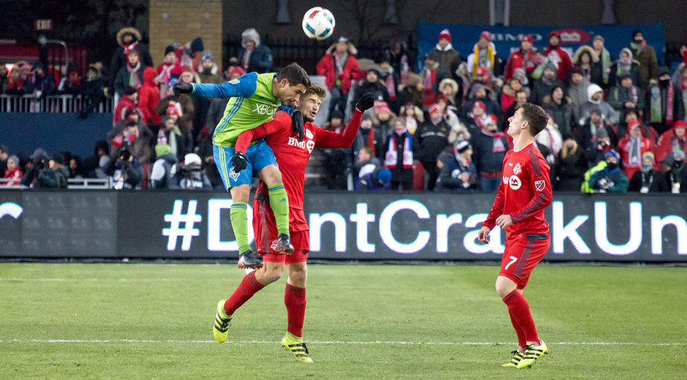 An aerial battle between Toronto FC and Seattle Sounders players during the MLS Cup Final. Photo by Dennis Marciniak.