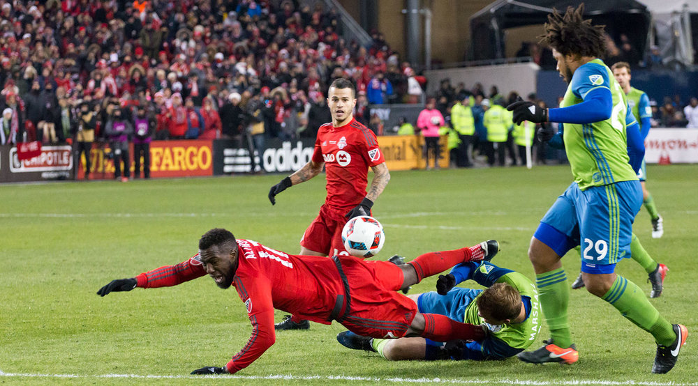 Jozy Altidore is taken to the ground as Sebastian Giovinco look on at the 2016 MLS Cup final in Toronto, Canada. Image by Dennis Marciniak.