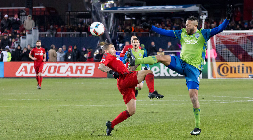 Tyrone Mears goes into a challenge with Sebastian Giovinco studs up at the 2016 MLS Cup final. Image by Dennis Marciniak.