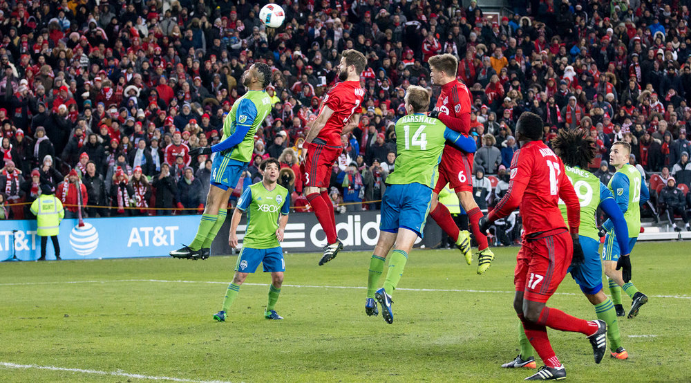 Seattle Sounders and Toronto FC players leap into the air trying to catch a ball during the 2016 MLS Cup Final. Image by Dennis Marciniak of denMAR Photography.
